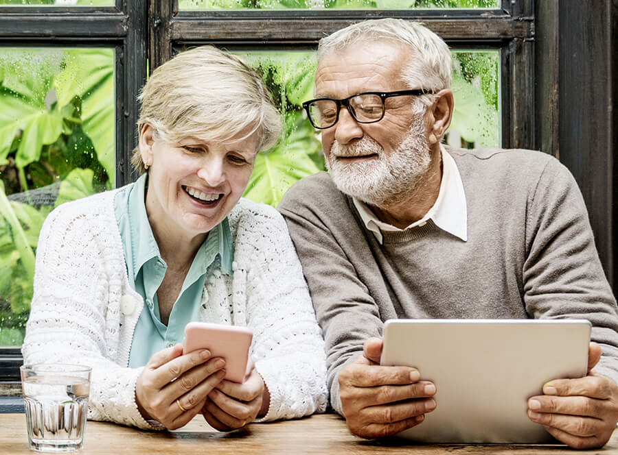 happy couple over 50 applying for life insurance on their mobile devices